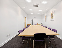 A Quality Formations conference room, complete with long meeting table, purple chairs and tasteful art.