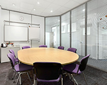 A Quality Company Formations conference room, complete with circular meeting table, purple chairs and a marker board.