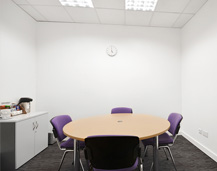 A Quality Formations conference room, complete with circular meeting table, purple chairs and storage facilities.