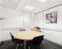 A Quality Formations conference room, complete with circular meeting table, purple chairs and tasteful art.